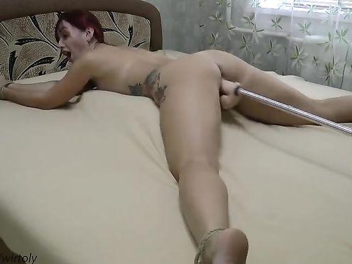 Привязанная к кровати телка наслаждается трахом с секс-машиной